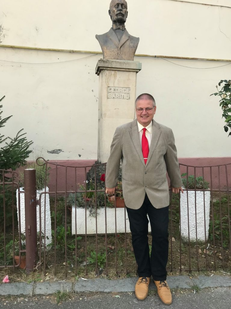 Il professor Laszlo Alexandru davanti alla statua di George Baritiu, a cui è dedicato il Colegiul National di Cluj, Romania