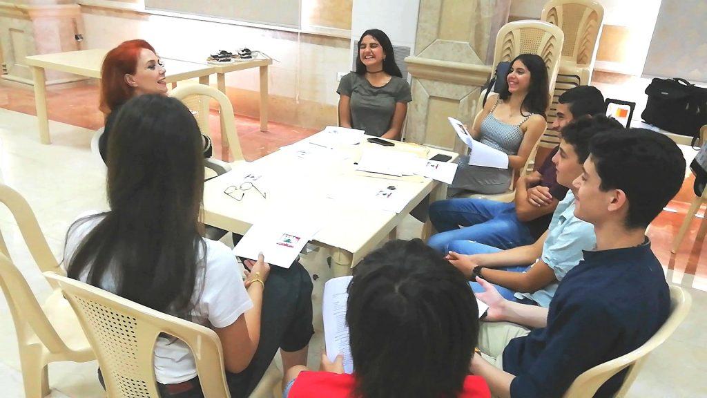 Laura Allegrini conversa con i ragazzi della scuola di Italiano, tutti seduti attorno a un tavolo