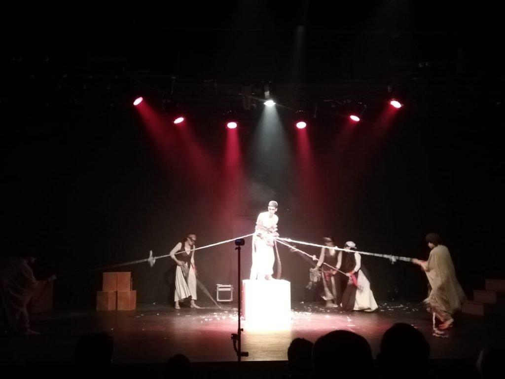Il giovane al centro interpreta il Libano trattenuto da corde tese da personaggi mascherati