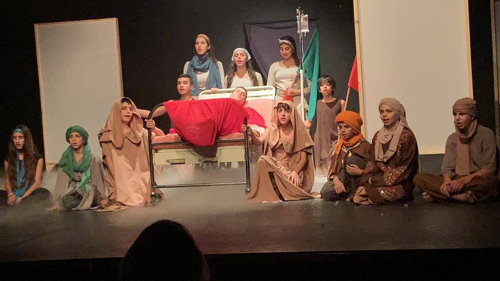 Il giovane che interpreta il Libano è su un letto ormai morente. Accanto a lui il popolo libanese lo esorta a reagire
